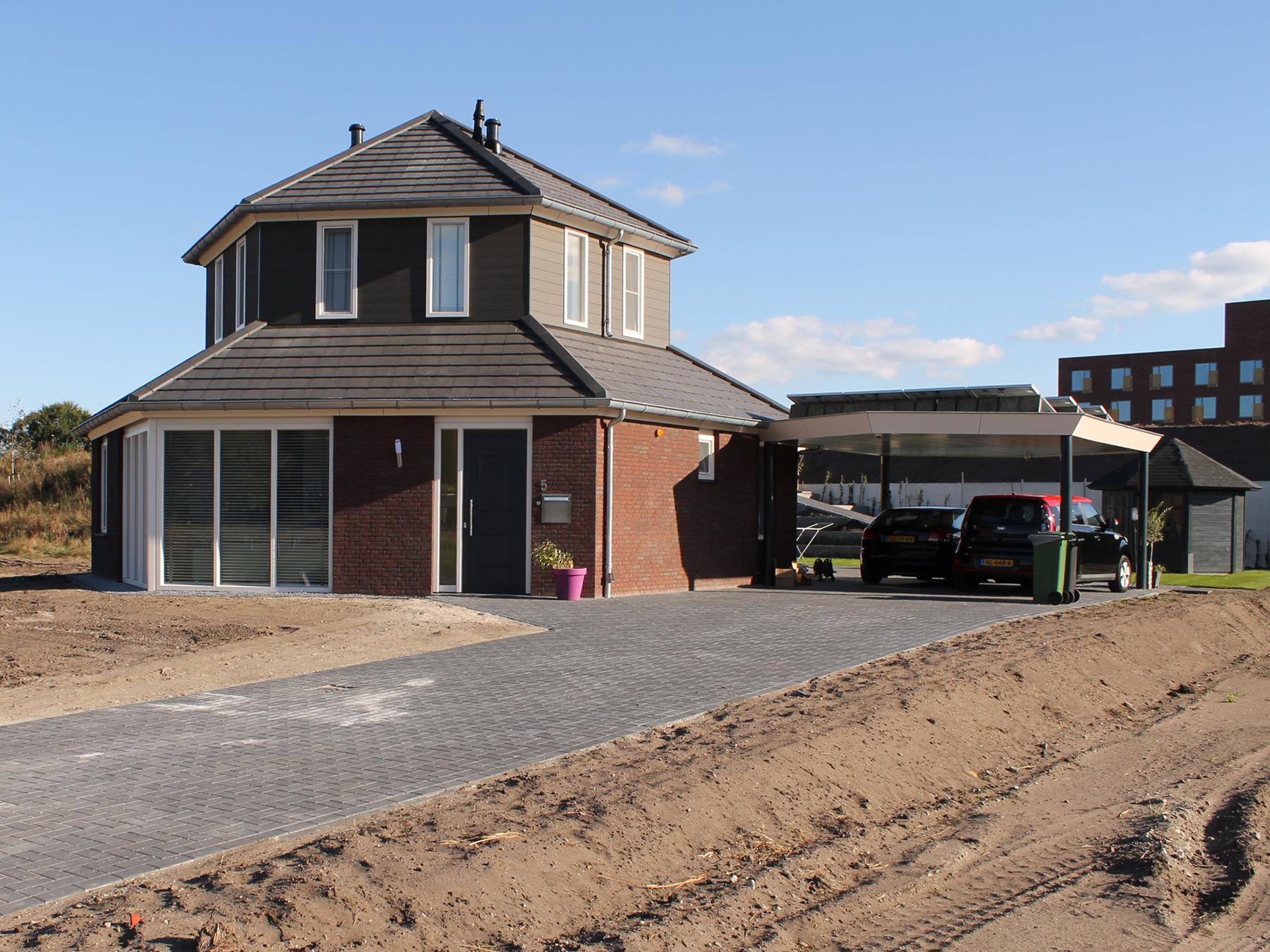 Een in prefab houtskeletbouw uitgevoerd zeskantig woonhuis met carport op park Maashorst te Uden.